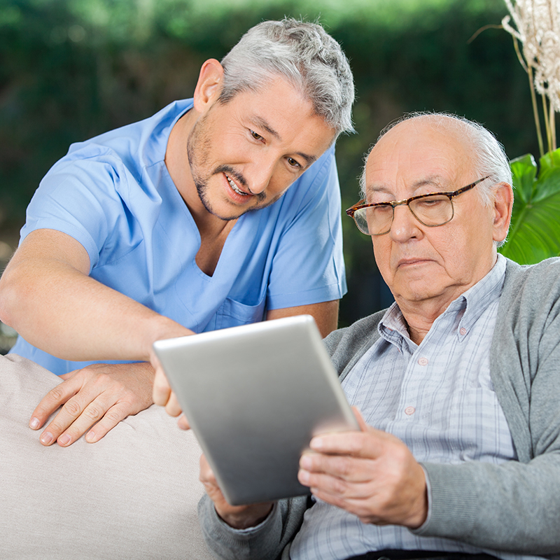Doctor helping older man access the internet on tablet
