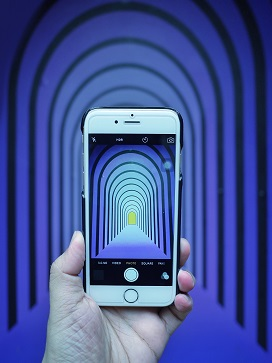 Smartphone held in front of repeating blue arches, with same image onscreen