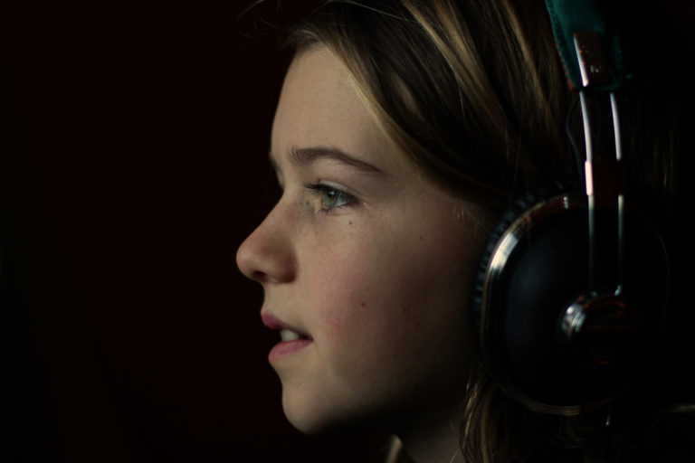 young girl wearing headphones looks to right against black background