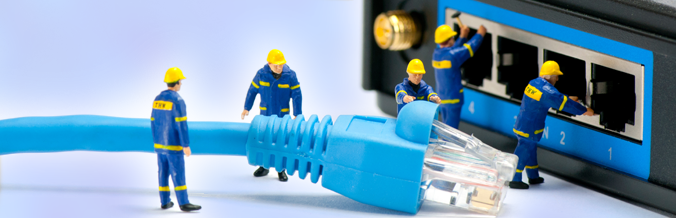Toy workmen inserting a cable into a modem