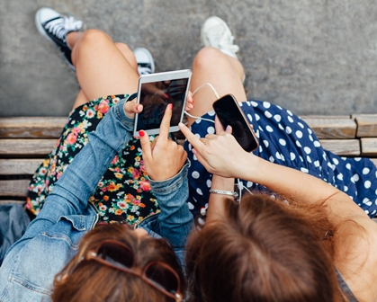 Teenage girls using smartphones