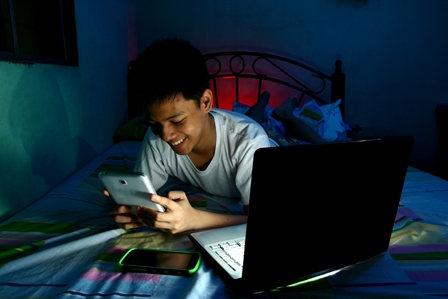 Boy using tablet, laptop and smartphone