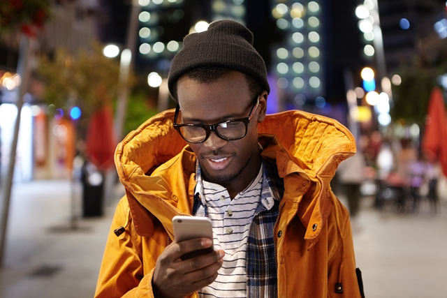 Man using smartphone on street at night