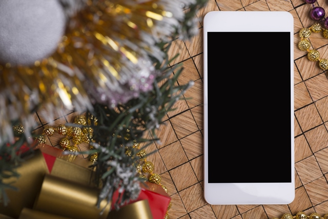 Smartphone next to Christmas tree