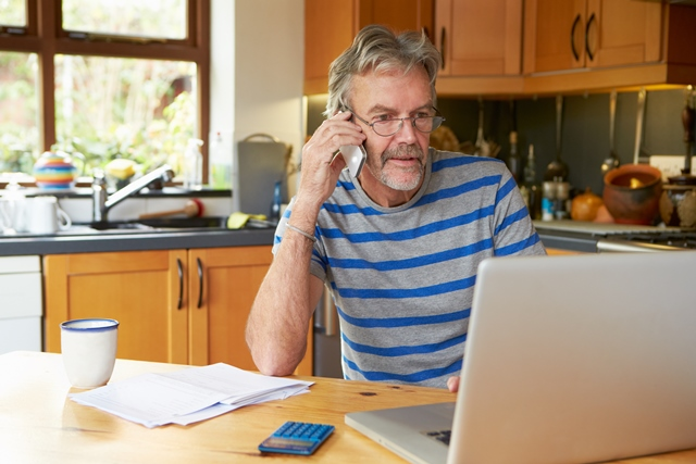 Man on telephone sitting in front of laptop