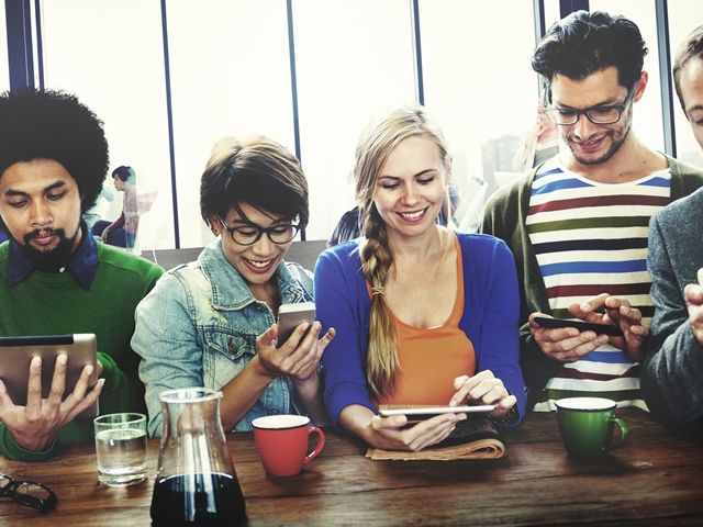 People at cafe using smartphones and tablets