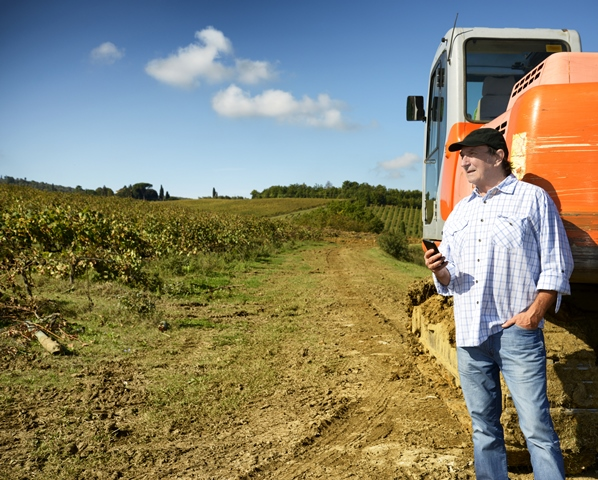 Farmer on phone standing next to bulldozer