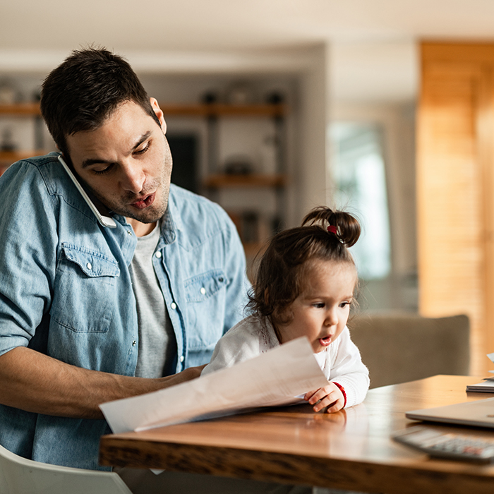 Man working at home with daughter on lap