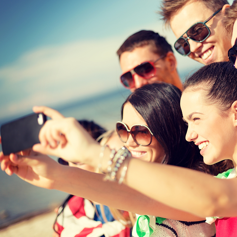 Group of friends taking selfie photo on phone