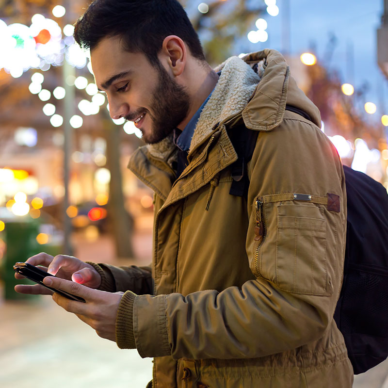 Man with backpack on street smiling at phone