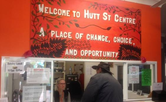 "Image of back of client speaking with staff member behind counter, under a red banner reading ""Welcome to Hutt St Centre. A place of change, choice and opportunity"""