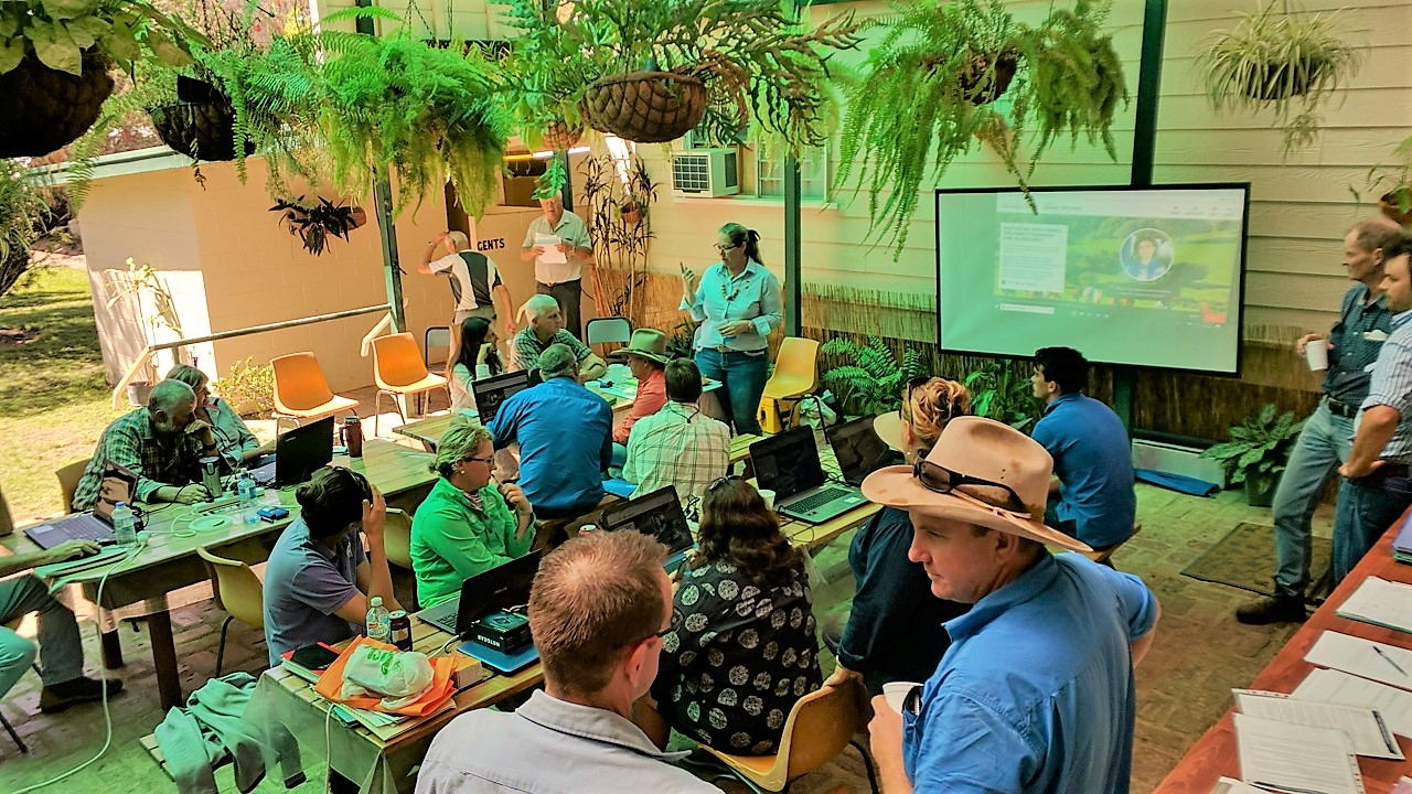 overhead view of farmers sitting & standing, chatting. Screen in front of them.
