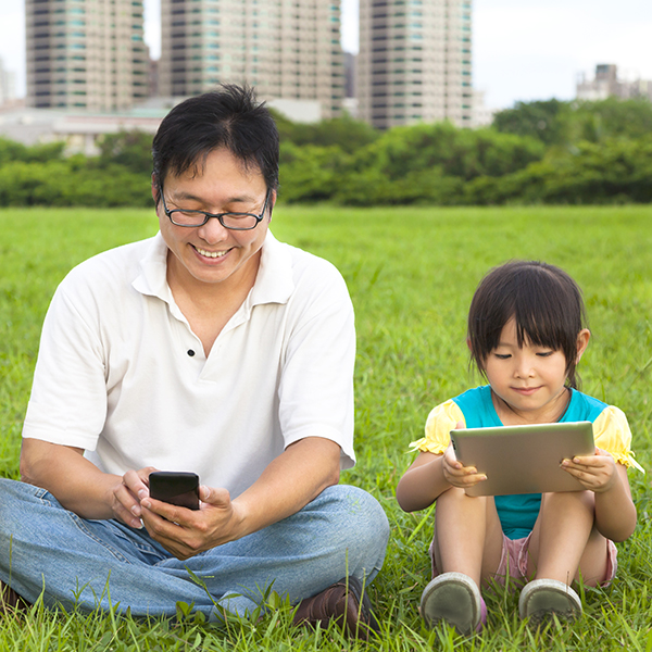 Father and daughter using mobiles in the park