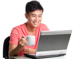 Picture of man holding coffee looking at laptop