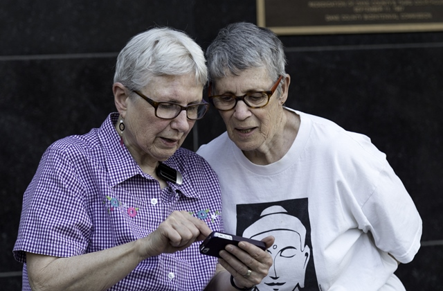 Older lesbian couple looking at smartphone