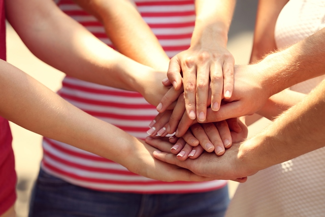 Group of people placing hands together in a circle