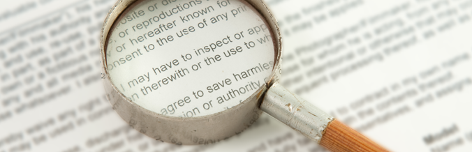 Magnifying glass close up on a contract's text