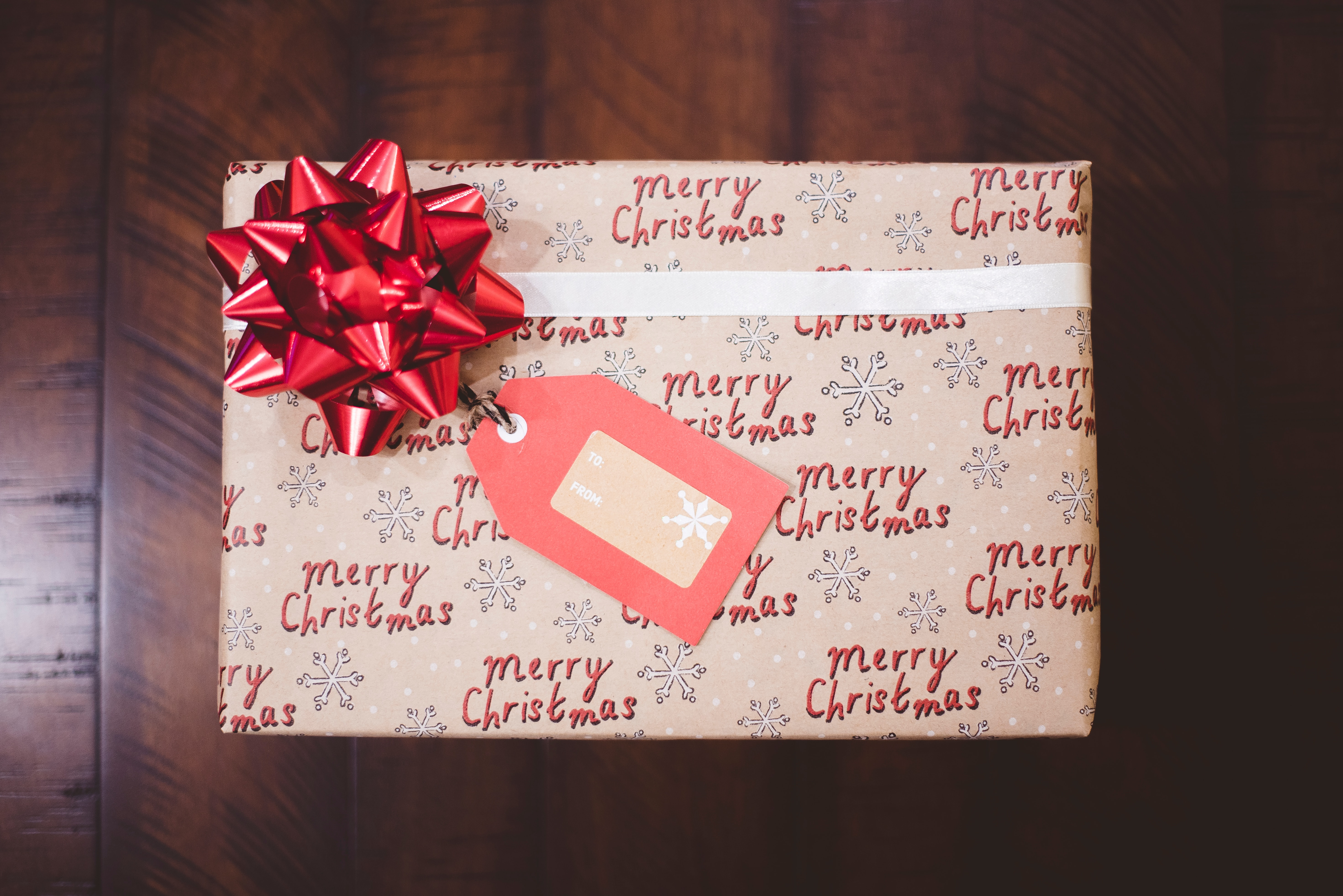 Image shows a rectangluar present with Merry Christmas printed across the wrapping paper. It has a red bow on the top left hand corner.